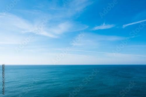Fotografia cloudy blue sky leaving for horizon above a blue surface of the sea