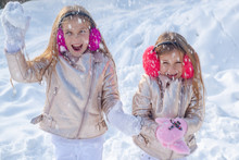 Little Girls Throw Snowball In Park. Theme Christmas Holidays Winter New Year. Two Adorable Young Girls Having Fun Together In Beautiful Winter Park.
