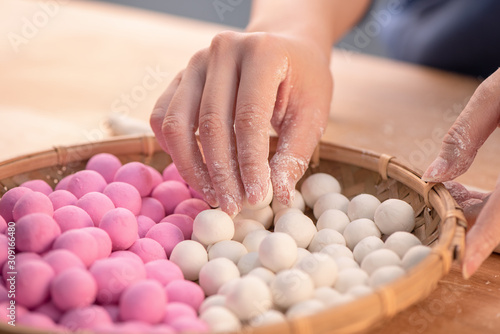 Obraz na plátně An Asia woman is making Tang yuan, yuan xiao, Chinese traditional food rice dumplings in red and white for lunar new year, winter festival, close up