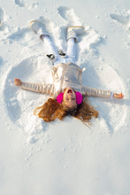 Girl On A Snow Angel Shows. Smiling Child Lying On Snow With Copy Space. Funny Kid Making Snow Angel. Top View.
