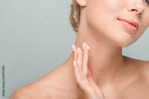 Obraz na plátně cropped view of woman applying cosmetic cream on neck isolated on grey