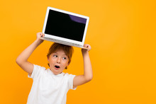 Surprised Boy Holds A Laptop O...