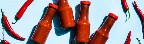 Photo Top view of bottles with chili sauce beside chili peppers on blue surface, panor