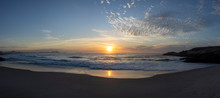 Super Wide Panorama Of Waves Coming In At The Arpoador Devil's Beach In Rio De Janeiro, Brazil, At Sunrise With The Sun Reflecting In The Water That Hits The Pristine Sand Beach With Scattered Clouds