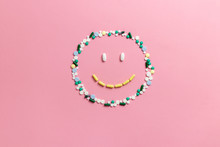 Composition Of Pills And Capsules On A Pink Background In The Form Of A Smile. Happy Emotions. Psychological Help. Copy Space. View From Above. Flat Lay.