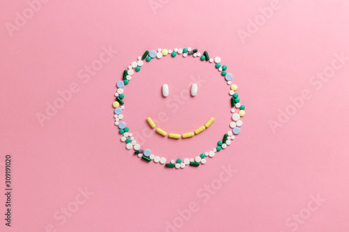 Composition of pills and capsules on a pink background in the form of a smile Wallpaper Mural