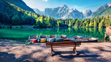 Six pleasure boats on Fusine lake. Spectacular morning scene of Julian Alps with Mangart peak on background, Province of Udine, Italy, Europe. Traveling concept background.