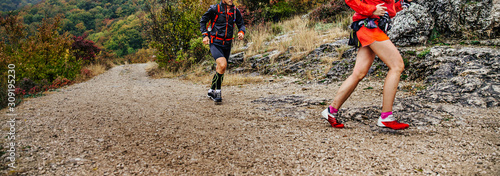 obraz PCV woman and man runners run mountain trail in autumn cloudy weather