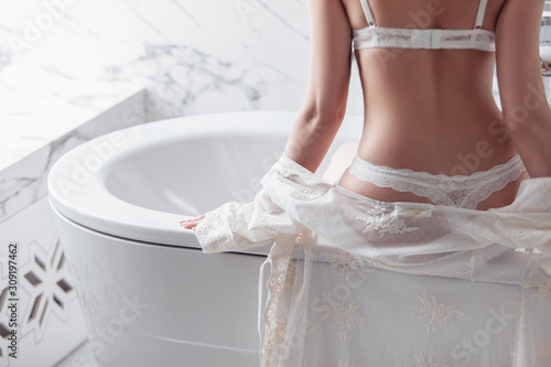 Obraz na plátně Rear view of a slim unidentified girl in white erotic lingerie sitting on the edge of the bathroom in luxury apartments