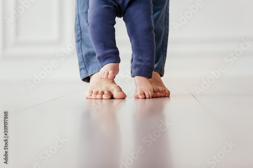 The bare feet of a young mother in blue pants are standing on the white floor next to the feet of a little one-year-old baby Fototapet