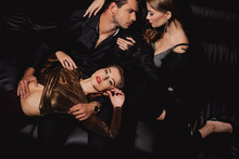 Top View Of Attractive Women Lying And Hugging Handsome Man Isolated On Black