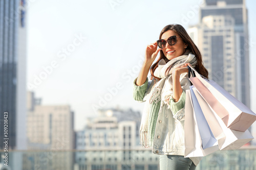 obraz dibond Beautiful young woman with shopping bags on city street