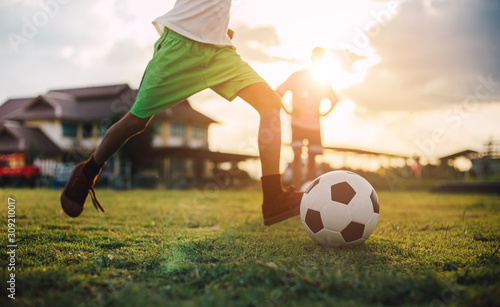 Silhouette action sport outdoors of diversity of kids having fun playing soccer football for exercise in community rural area under the twilight sunset sky Canvas Print