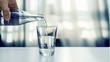 Nalewanie oczyszczonej świeżej wody do picia z butelki na stole w salonie