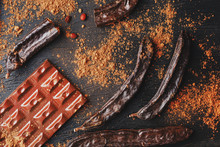 Carob Chocolate And Carob Fruit Powder On Dark Background. A Tasty And Useful Substitute For Chocolate.