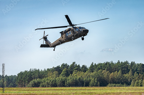 Military helicopter flying in the sky with forest at the background Canvas Print