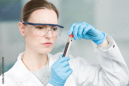 Fotografia Female scientist with medical gloves and safety glasses is handling a blood prob