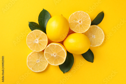 Fotografía  Juicy lemons and leaves on yellow background, top view