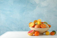 Juicy Citrus Fruits In Bowl On Wooden Table Against Blue Background, Space For Text