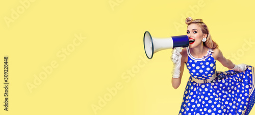 Fotografía Retro, vintage  and holiday sales concept picture- Woman holding megaphone, dressed in pin up style blue dress, over yellow background
