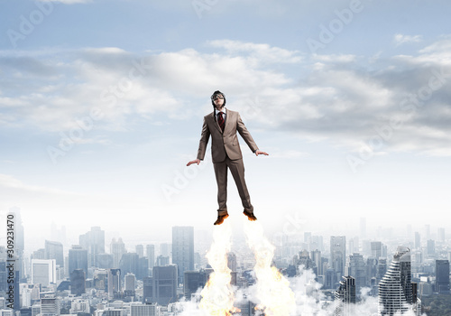 Businessman in suit and aviator hat flying in sky Fototapeta