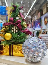Sparkling Christmas Ball With Blurred Christmas Tree With Gifts On Background. Vertical Position. New Year Decoration. Christmas Backdrop. Artificial New Year Tree With Golden Balls And Burgundy Bows