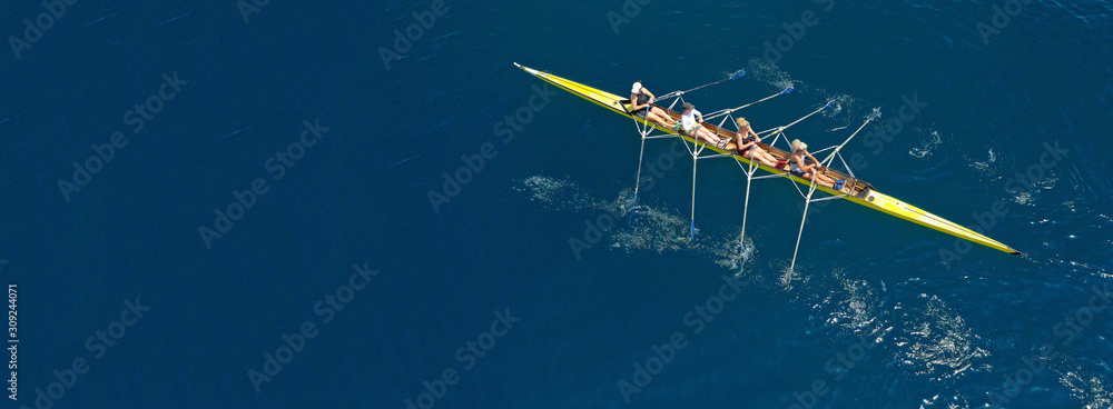Fototapeta Aerial drone ultra wide photo of team of fit women practising in sport canoe in deep blue open ocean sea