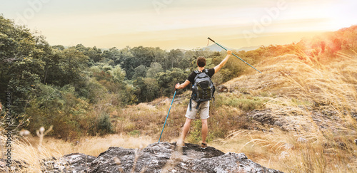 Fototapeta Rear view of standing man with raised up arms and holding trekking pole on the stone and looking to forest and peak of mountains. Landscape Lifestyle travel, Success and Achievement concept. obraz