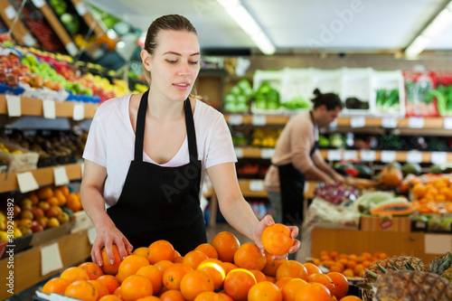 Young woman wearing apron working with fresh oranges Canvas Print