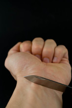 Man Want To Commit Suicide By Cutting His Veins With Sharp Knife. Close Up Hands