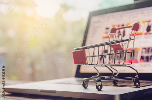 Shopping online concept - shopping cart or trolley on a laptop keyboard. Shopping service on The online web. offers home delivery..