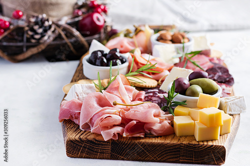 Antipasto platter with ham, prosciutto, salami, cheese,  crackers and olives on a light background Wallpaper Mural