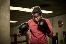 Determined Female Boxer Practi...