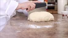 Chef Cutting Fresh Bread Dough Into Portions Using A Bench Scraper.