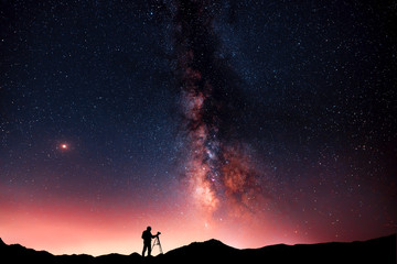 Beautiful starry night landscape. A silhouette of a photographer stands on a hill and looks at a beautiful starry sky with a bright milky way