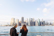 Young couple looking at Manhattan skyline from Brooklyn