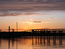 Sunset Glowing Over A Dock Leading Out To Water Of Puget Sound