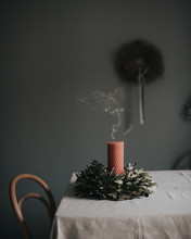 Blown Out Candle With Wreath On Table