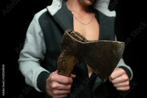 Photo A man with an ax in his hand comes out of the dark, selective focus, close-up