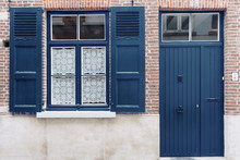 Old House Exterior With Blue Painted Door And Window Shutters. Classic Blue 2020 Year Color Trend Concept