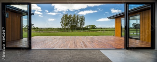 Fototapeta View from a modern house with big glass doors looking at the green field obraz