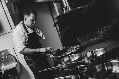 Head chef cooks prepares food,grill, in a restaurant in a kitchen, bw, black&white