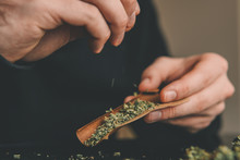 Close Up Marijuana Joint With Lighter. Man Rolling Marijuana Cannabis Blunt. Man Rolling A Marijuana Weed Blunt.
