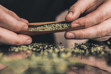 Man Rolling A Marijuana Weed Blunt. Man Rolling Marijuana Cannabis Blunt. Close Up Marijuana Joint With Lighter.