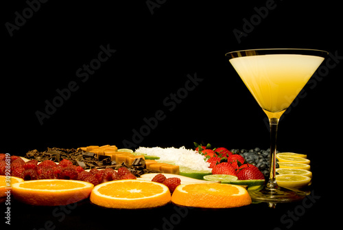 Yellow cocktail with fruit pieces on black background