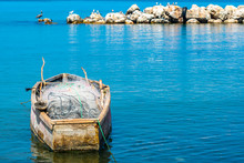 Empty Old Wooden Fishing Boat With Net And Rods, Docked & Floating In Sea Water. Coastal Ocean View With Birds Perched On Large Sea Rocks/ Boulders In The Background. Sunny Summer Tropical Island Day.