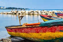 Colorful Empty Old Wooden Fishing Boats Docked By Sea Water In Sand On Shore. Coastal Ocean View With Birds On Large Rock Boulders In Background. Sunny Summer Tropical Caribbean Island Day Outdoors.