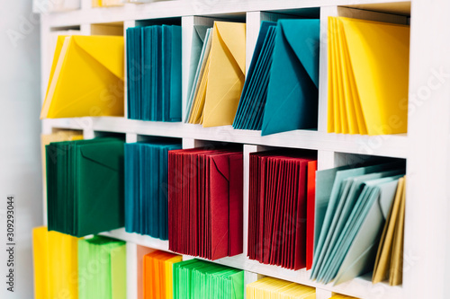Fototapeta Colored sort mail envelopes arranged on a shelf by color and type categories.  obraz