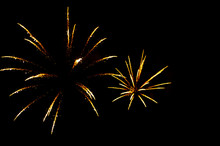 Two Yellow Fireworks In The Shape Flowers On The Black Background.
