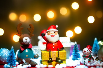 Santa Claus doll, pine tree, deer, snowman and gift box merry Christmas decoration on a bokeh light background with copy space